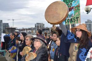 protestors march with drums and signs