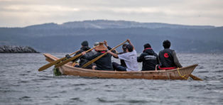 first nations paddling a canoe