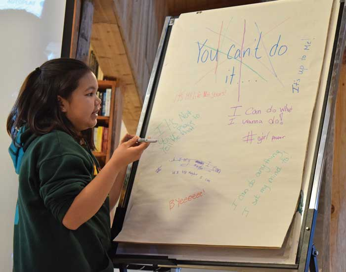 girl writing on flip chart