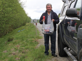man collecting cans beside highway
