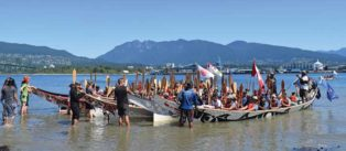 canoes arrive after Pulling Together Canoe Journey