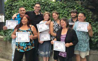 graduates hold up certificates